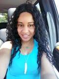 Jolie femme bouclée de cheveux noirs conduisant une voiture image stock
