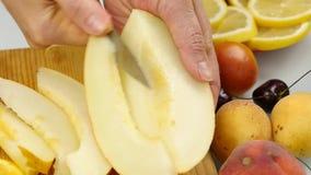 Jolie femme coupant en tranches le melon de miellée sur la planche à découper Perte de poids et concept suivant un régime Mouveme banque de vidéos
