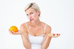 Jolie femme décidant entre la pizza et une orange image stock