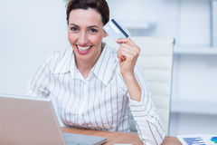 Jolie femme d'affaires de brune employant la carte de crédit photographie stock