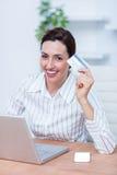 Jolie femme d'affaires de brune employant sa carte de crédit images libres de droits