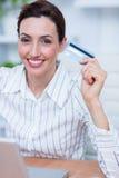 Jolie femme d'affaires de brune employant sa carte de crédit photos stock