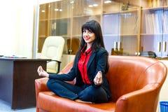 Jolie femme d'affaires de sourire s'asseyant sur le sofa dans le posi de lotus Photographie stock