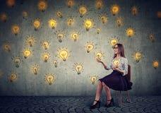 Jolie femme d'affaires jonglant avec les ampoules image stock