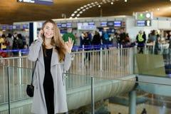 Jolie femme d'affaires parlant par le smartphone au hall d'aéroport, au manteau gris de port et montrant correct Image stock