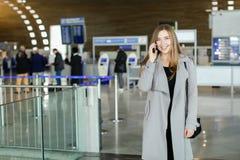 Jolie femme d'affaires parlant par le smartphone au hall d'aéroport, au manteau gris de port et au sac Photos stock