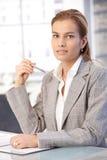 Jolie femme d'affaires s'asseyant au bureau Images stock