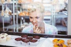 Jolie femme d'hésitation regardant des gâteaux de tasse image stock