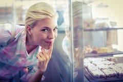 Jolie femme d'hésitation regardant des gâteaux de tasse photo libre de droits