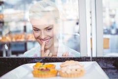 Jolie femme d'hésitation regardant le tarte de fruit photographie stock libre de droits