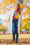 Jolie femme dans de grandes feuilles blanches de participation de manteau photos libres de droits