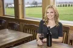 Jolie femme dans l'établissement vinicole ou barre avec le vin rouge Photographie stock