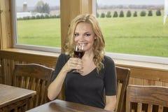 Jolie femme dans l'établissement vinicole ou barre avec le vin rouge Image libre de droits