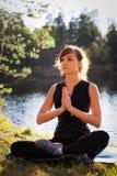 Jolie femme dans la pose de yoga de salutation de Namaskarasana Photographie stock libre de droits