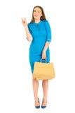 Jolie femme dans la robe bleue posant avec des sacs Photographie stock libre de droits