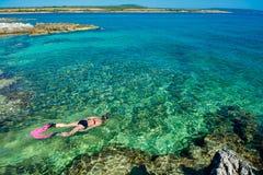 Jolie femme dans le bikini naviguant au schnorchel par l'eau de turquoise à la côte de la Croatie Image libre de droits