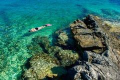 Jolie femme dans le bikini naviguant au schnorchel par l'eau de turquoise à la côte Photo libre de droits