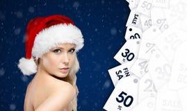Jolie femme dans le chapeau de Noël avec la grande offre saisonnière Image stock