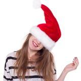 Jolie femme dans le chapeau rouge du père noël riant sur le fond blanc Image libre de droits