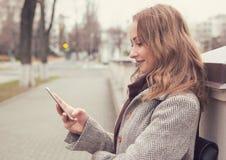Jolie femme dans le manteau se reposant sur la rue utilisant le téléphone et le sourire futés Images stock