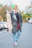 Jolie femme dans le vêtement occasionnel frais avec la planche à roulettes Image stock