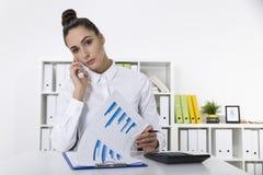 Jolie femme dans un chemisier blanc sur son mobile dans un lookin de bureau Photos stock