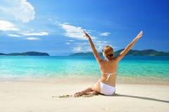 Jolie femme dans une bonne humeur exposant au soleil sur la plage sablonneuse blanche Image libre de droits