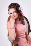 Jolie femme dans une robe rose avec des fleurs dans son sourire de cheveux Photographie stock libre de droits