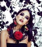 Jolie femme de brune avec m de bijoux, noir et rouge, lumineux rose image libre de droits