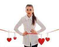 Jolie femme de brune dans l'amour posant avec le coeur rouge sur le fond d'isolement sur le fond blanc Photos libres de droits