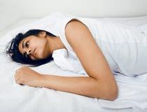 Jolie femme de brune dans le lit, sommeil biseauté Photographie stock