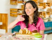 Jolie femme de brune s'asseyant par la table à l'intérieur de la boulangerie, supportant le verre à liqueur chaud d'expresso et p Photos stock