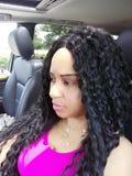 Jolie femme de cheveux bouclés dans la photographie de voiture de vue de côté portant un dessus rose image libre de droits