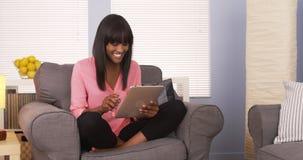 Jolie femme de couleur à l'aide du comprimé dans la chemise rose Photo stock
