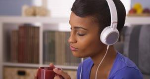 Jolie femme de couleur écoutant la musique avec des écouteurs Images stock