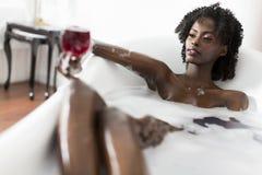 Jolie femme de couleur ayant un bain photographie stock libre de droits