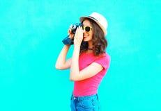 Jolie femme de mode prenant le chapeau d'été de paille de photo, les lunettes de soleil et l'appareil-photo de port de vintage au Photos stock