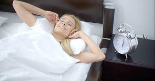 Jolie femme de sommeil avec le réveil à côté de elle banque de vidéos