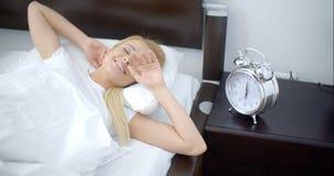 Jolie femme de sommeil avec le réveil à côté de elle clips vidéos