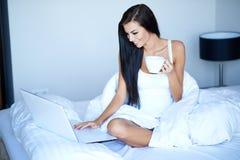 Jolie femme de sourire à l'aide de l'ordinateur portable sur le lit photos stock