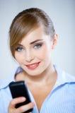 Jolie femme de sourire à l'aide du téléphone portable noir photographie stock