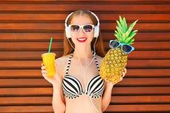 Jolie femme de sourire avec la tasse drôle de jus d'ananas et de fruit photos stock
