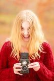 Jolie femme de sourire avec le vieil appareil-photo de vintage Photos stock