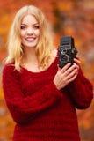 Jolie femme de sourire avec le vieil appareil-photo de vintage Photos libres de droits