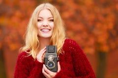 Jolie femme de sourire avec le vieil appareil-photo de vintage Photographie stock libre de droits