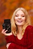 Jolie femme de sourire avec le vieil appareil-photo de vintage Images stock