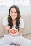 Jolie femme de sourire dans des pyjamas mangeant de la céréale fruitée Photos libres de droits