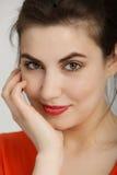 Jolie femme de sourire dans l'orange avec la main sur le visage Photographie stock libre de droits