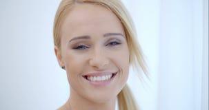 Jolie femme de sourire derrière le rideau blanc banque de vidéos