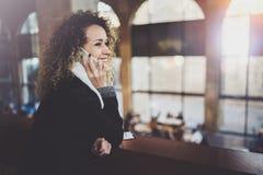 Jolie femme de sourire parlant avec des amis par son téléphone de cellules Bokeh et effet de fusées sur le fond brouillé Photos stock